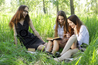 three students reading books outdoor