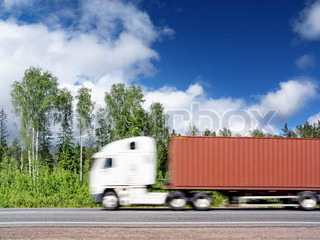 white container truck speeding on country highway, blured in motion