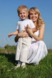 The mother and son. Happy people on a meadow with the clear blue sky