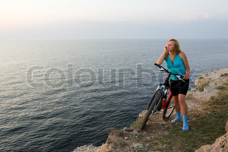 Girl with her bike relaxing and watching sunset near the sea.