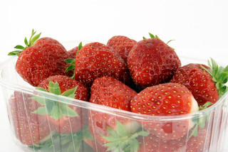 ripe strawberries in plastic container against white background