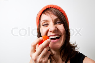 Young woman tomato in hand smiling. Studio shot.