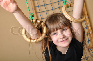 6 year old girl  playing at her home wooden gym