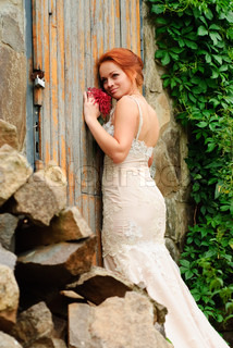 Glamour bride in beige dress stand near the old locked door and with ivy