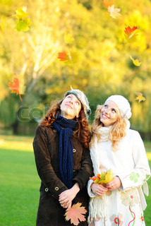 Two girl under the maple tree look on falling leaves