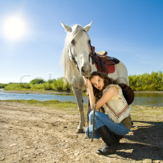 young cowgirl with white horse outdoor