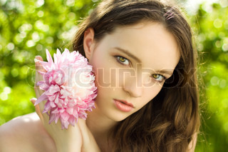 pretty teenager girl with flower on green background close-up