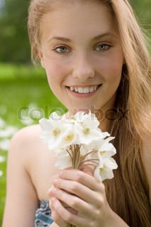 portrait of pretty teen girl with white flowers in the park