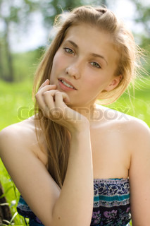 portrait of beautiful teen girl with hand near the face in the park
