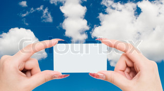 greeting card in a hand on a sky background