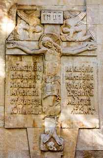 Crucifix on the wall of ancient temple. The text on a bas-relief means: