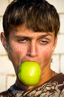 Portrait of a guy with the streaking hair, biting an apple