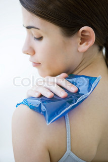 ©Alix Minde/AltoPress/Maxppp ; Woman placing cold compress on shoulder, close-up