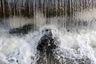 The jets of water falling on rocks, splashes and foam.