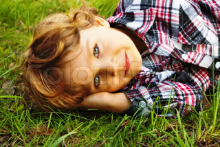 Portrait of a little smiling  boy lying in the grass