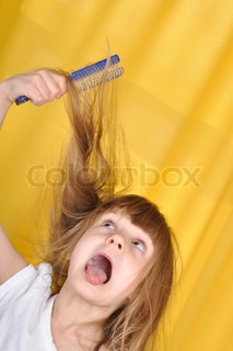 little girl trying to brush her hair with a hairbrush