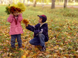 Young boy giving young girl bouquet of autumn leafs and smiling