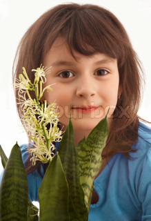 Smiling little girl with blooming home plant Sansevieria