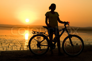 Silhouette girl with bicycle nera the sea, travel concept.