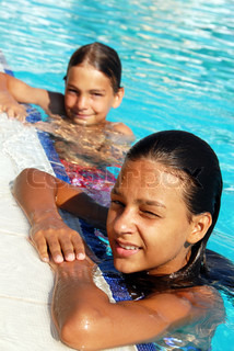 smiling girl and boy in blue swimming pool portrait