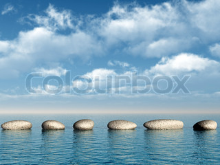 A row of stones in water. A pebble on a background of the sky