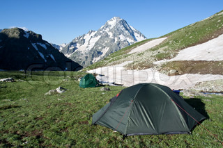 Camping tents on sunny grassland,travel background.