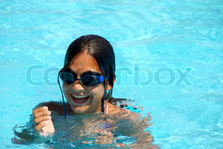 happy teen girl with goggles blue swimming pool portrait
