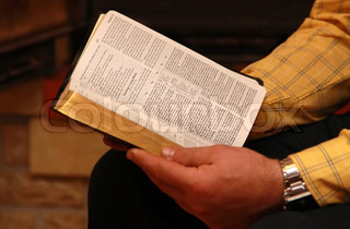 A man reads the Bible at home sitting in a chair