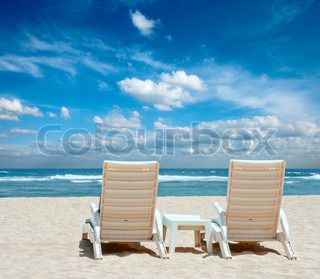 Two sun beach chairs on shore near ocean
