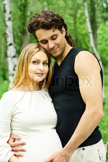 Beautiful pregnant woman with her husband in the park