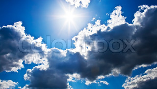 Bright sunrays in a blue cloudy sky