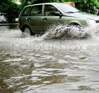 En bil stænk gennem en stor vandpyt på en våd vej.
