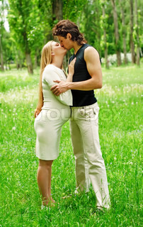 Beautiful pregnant woman with her husband kissing in the park