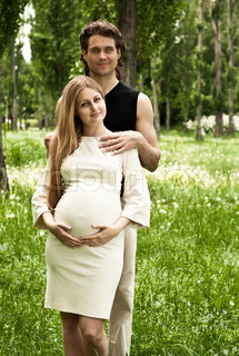 Happy beautiful pregnant couple in the park