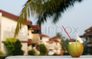 fresh coconut drink with strow on the table