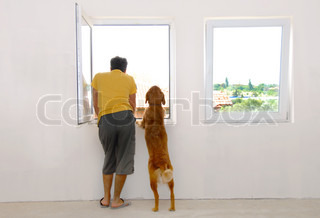 man and his dog looking through window back view