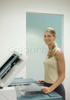 ©Odilon Dimier/AltoPress/Maxppp ; Female office worker standing at copy machine, smiling at camera