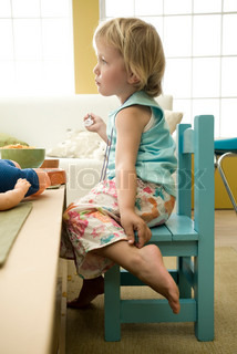 ©Laurence Mouton/AltoPress/Maxppp ; Toddler girl sitting at table, touching ankle, side view