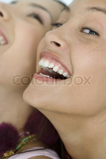 ©Laurence Mouton/AltoPress/Maxppp ; Two young female friends laughing, one looking at camera, extreme close-up of faces, cropped