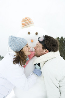 ©Laurence Mouton/AltoPress/Maxppp ; Young couple leaning towards each other in front of snowman, smiling, portrait