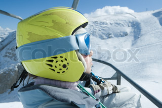 ©Laurence Mouton/AltoPress/Maxppp ; Young skier riding ski lift, wearing helmet, side view