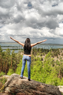 Female at the top of mountain with beautiful sky