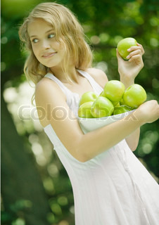 ©Rafal Strzechowski/AltoPress/Maxppp ; Woman holding bowl of apples, looking over shoulder