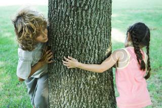 ©Eric Audras/AltoPress/Maxppp ; Girl and boy standing on either side of tree trunk, peeking around