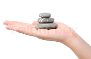 balancing stones on a hand over white