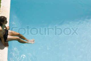 ©Michèle Constantini/AltoPress/Maxppp ; Man sitting on edge of swimming pool, soaking feet in water, high angle view