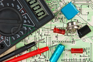 multimeter  and electronic components on circuit