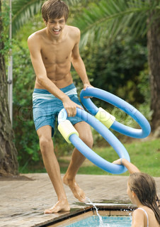 ©Odilon Dimier/AltoPress/Maxppp ; Adolescent boy playing with younger sister at swimming pool