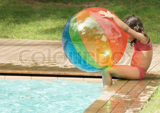 ©Odilon Dimier/AltoPress/Maxppp ; Little girl sitting on edge of swimming pool, holding beach ball