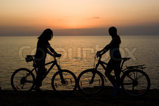Boy and girl where riding there bikes, and watching sunset on the sea.